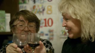 Old and middle-aged women toasting and drinking red wine at home.