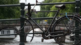 Old Bicycle With Amsterdam Canal In Distance