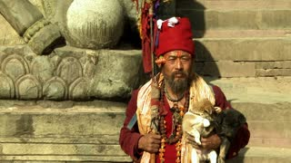 Old Nepali Man Holding Puppies on Stone Steps