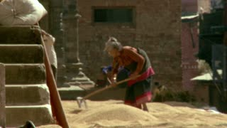 Old Woman Sorts Sand in Village in Nepal