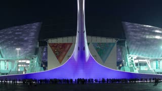 Olympic Torch with fountains in light in Olympic park fisht stadium in the background timelapse. Sochi, Russia 4K