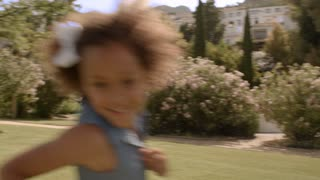 One child running around camera in park