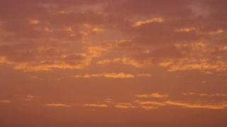 Orange Sunset Speckled With Clouds