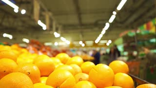 Oranges and unrecognizable customers in supermarket. Slow motion video