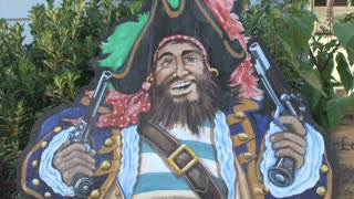 Painted Pirate Sign Next to Bench