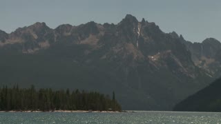Pan Across Lake and Snow Speckled Rocky Mountain Peaks
