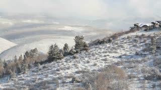 Pan Across Snowy Landscape to Hilltop Cabin