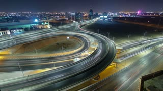 Pan and tilt Cityscape of Ajman with traffic on main road overpass from rooftop at night with lights timelapse fisheye. Ajman is the capital of the emirate of Ajman in the United Arab Emirates. 4K