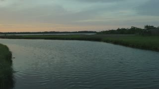 Pan around a river inlet with distant sunset
