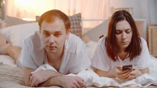PAN of annoyed young man lying on bed with his wife holding mobile phone and arguing about something