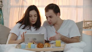 PAN of laughing young woman and man sitting in bed on early Sunday morning eating breakfast and watching something on tablet