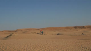 Pan of People Walking In Desert