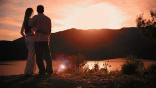 Pan shot of couple standing in park overlooking lake in sunset