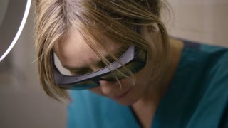 Panning down shot of doctor or therapist administering fractional skin laser treatment to resurface and rejuvenate a womans skin