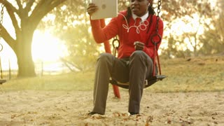 Panning shot of African American man using tablet computer for video chat while on a park suing at sunrise.