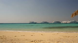 Panning shot of beautiful tropical scene with pure sea, straw sun umbrella and luxurious yachts in the distance