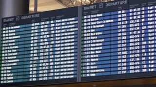 Panning shot of digital flight schedule at the aiport. It is shown on four big displays