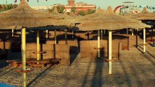 Panning shot of empty beach area with straw sun umbrellas. Focus on the sea at the end