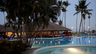 Panning shot of tropical resort area in the evening. It including swimming pools, restaurant and place for sunbathing with chaise-longues and sun umbrellas