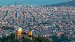 Panorama of Barcelona timelapse with palace on hill from Mount Tibidabo before sunset. Catalonia, Spain. Shadow move over the city. 4K