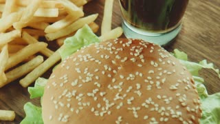 Panoramic view of cola or soda in the glass, french fries potato and hamburger sandwich on tray on table