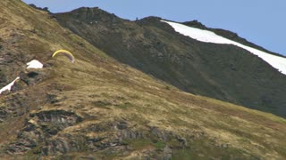 Paraglider Soaring By Mountains