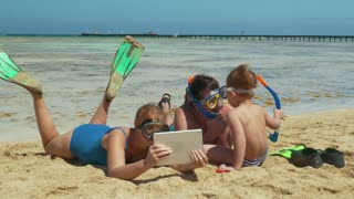 Parents and their son are lying on the beach after snorkel diving. They are watching something in tablet PC and talking.