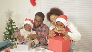 African American parents helping children assemble christmas gifts ...