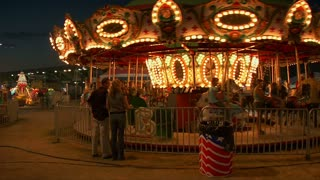 Parents Watch Their Kids On Carousel
