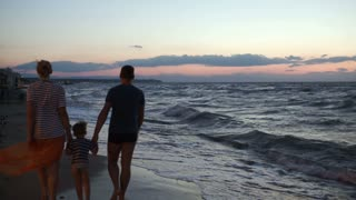Parents with son walking barefoot along the shore in the evening. They holding hands, waves washing their feet