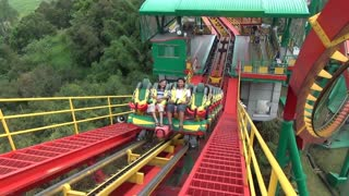 Passengers on Roller Coaster Incline Wave at Camera