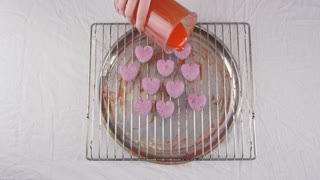 Pastry-cook puts prepared candies in the form of hearts on tray