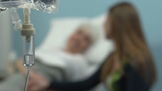 Patient being consoled by her Granddaughter. The granddaughter talks to her grandmother and holds her hand. Rack focus