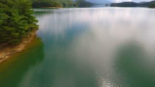 Peaceful flight over an emerald lake backward 2