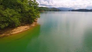 Peaceful flight over an emerald lake backward