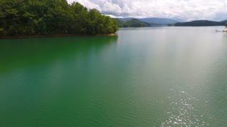 Peaceful flight over an emerald lake forward