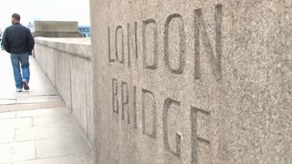 Pedestrians Walking Past London Bridge Sign