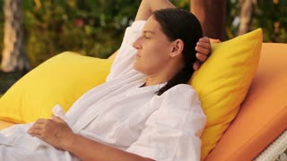 Pensive woman lying on bed in garden, steadycam shot
