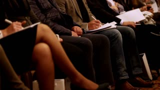 people at a conference or presentation, workshop, master class - legs and arms, close up