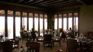 People Dine In Restaurant With Large Windows