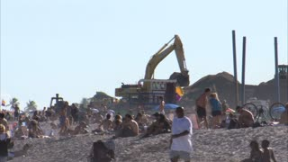 People Laying on Beach with Bulldozers and Construction Equipment