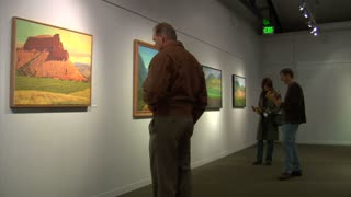 People Look At Paintings In  Art Gallery