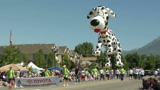 People marching in the parade with a spotted dog float