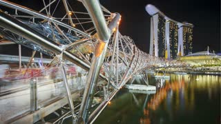 People on the illuminated Helix Bridge and Marina Bay Sands Singapore. Marina Bay, Singapore, Asia, Time lapse