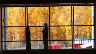People Talk Near Large Windows With Fall Leaves