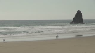 People Walking on Cannon Beach Shoreline