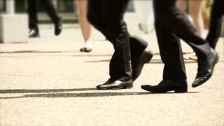 people walking synchronized together. feet foot. slow motion. business people