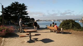 People Watch Kayaker And Sailboat On The Shore Of Monterey Bay