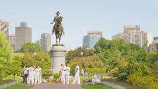 People Wearing White in Front of Boston Statue