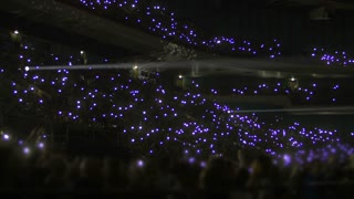 Performance in the stadium at night. Crowd of people on stands waving with small flashlights